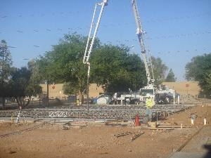 Workers supervise concrete truck pumping basketball court