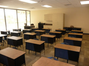 Elementary charter school classroom seen from the front. Sunny window overlooks the teacher desk in the back of the class.