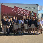 7th grade boys and girls in school uniforms in front of food pantry truck