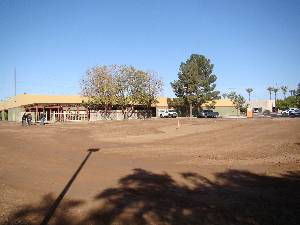 Expanse of smooth dirt playground outside elementary school building