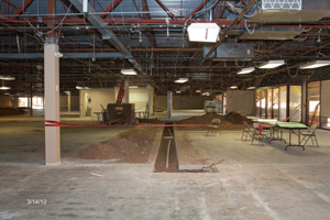Inside gutted building with folding tables and chairs for charter school construction meeting