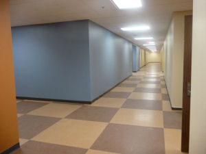 Long interior hallway with tan and brown checkered tile and sky blue walls
