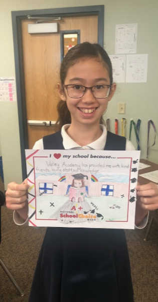"Smiling girl with glasses holds sign ""Valley Academy has provided me with kind friends, loving staff, and knowledge!"