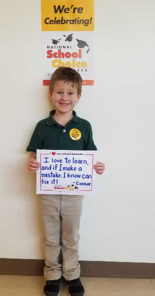 "Smilling kindergarten boy holds sign ""I love to learn, and if I make a mistake, I know I can fix it --Connor"""