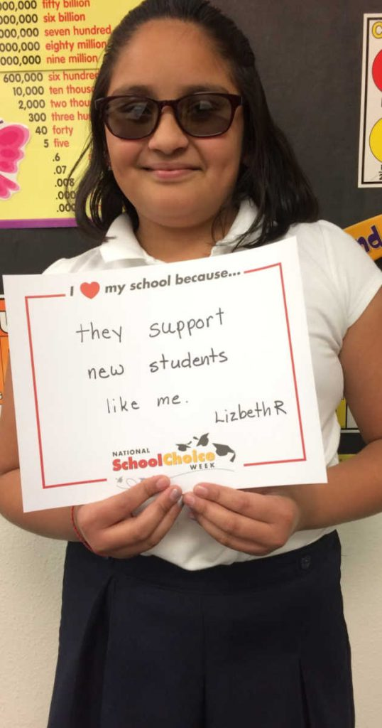 "MIddle school girl with dark glasses holds sign ""I love my school becuase they support new students like me. __Lizbeth R."""